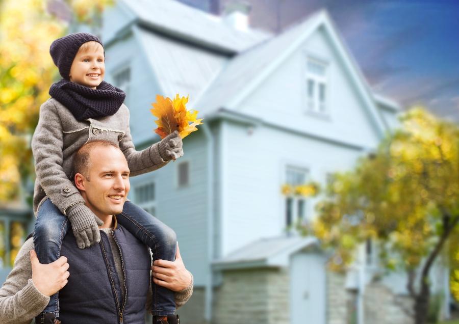 padre con hijo junto a casa en otoño