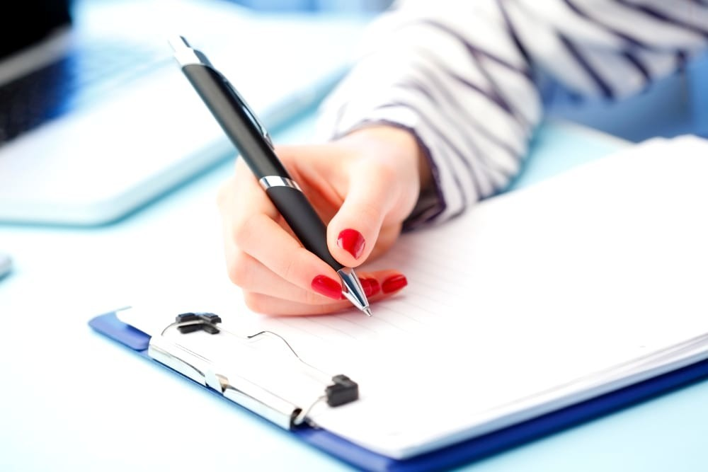 persona escribiendo estatutos comunidad de propietarios