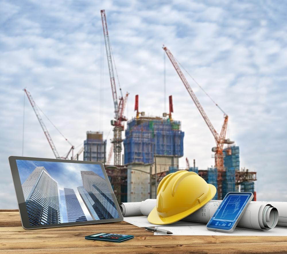 edificio en construcción con herramientas y ordenador en primer plano