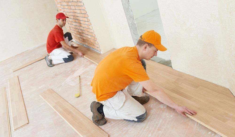 obreros instalando tarima piso obra nueva