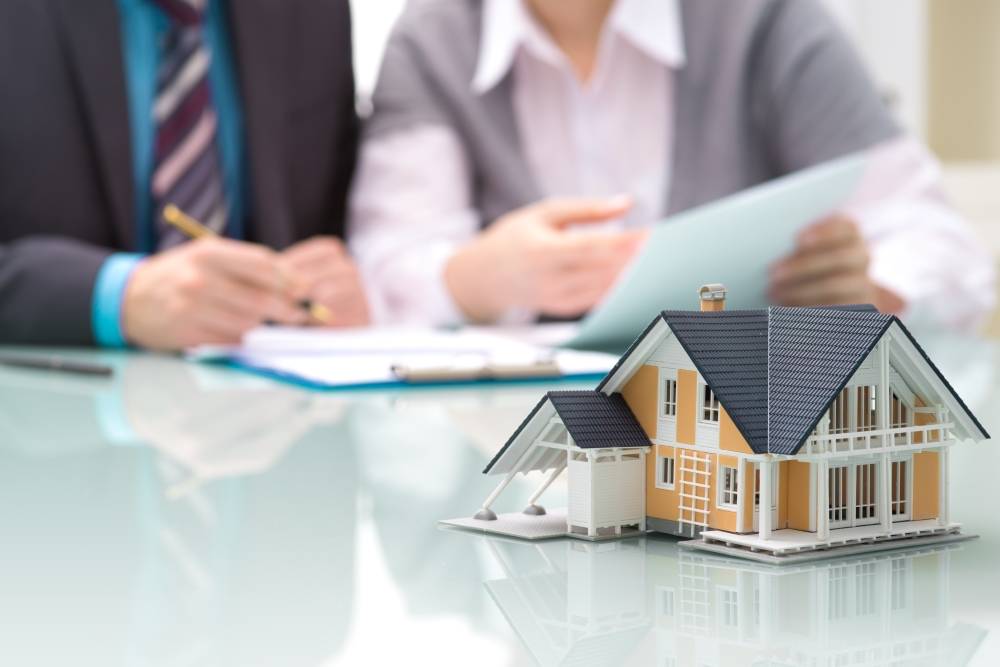 maqueta de casa sobre mesa y personas firmando hipoteca