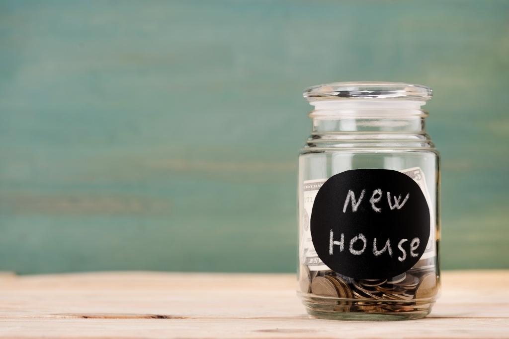 bote de cristal con dinero necesario para comprar una casa