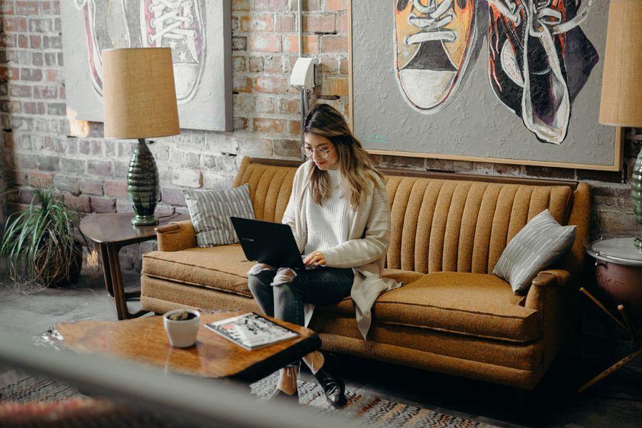 chica con ordenador sentada en el sofá del salón