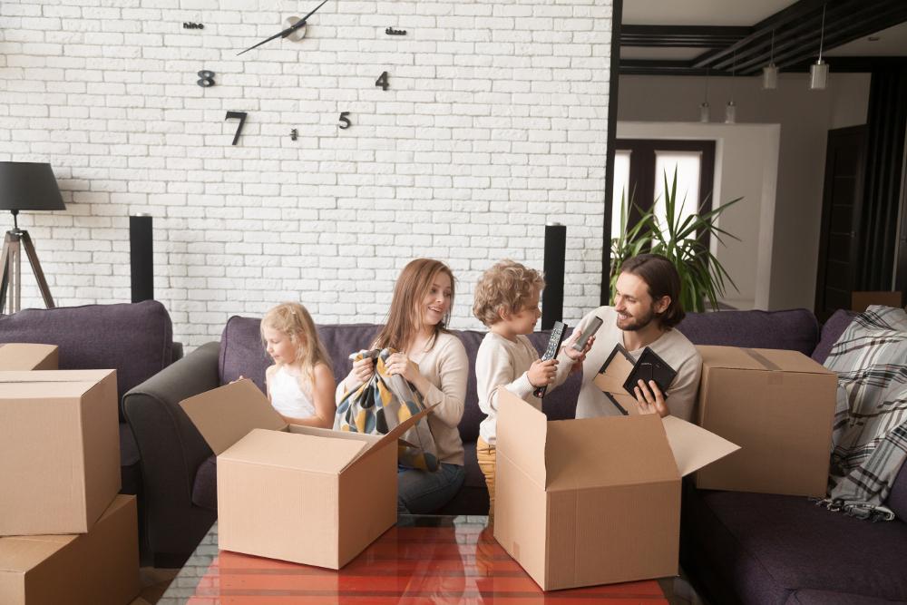 pareja con hijos haciendo mudanza en un piso de obra nueva