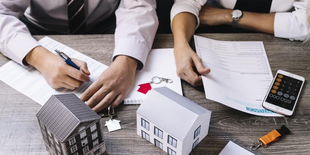 firma de documento y maqueta de una casa
