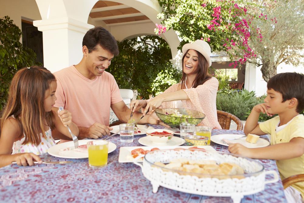 familia comiendo en jardín de segunda vivienda