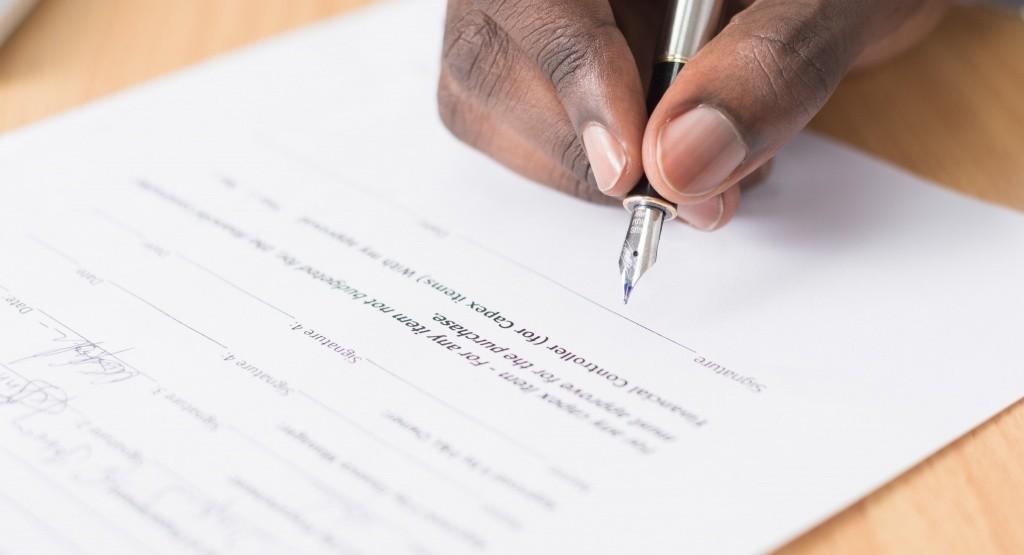 persona firmando contrato para una hipoteca