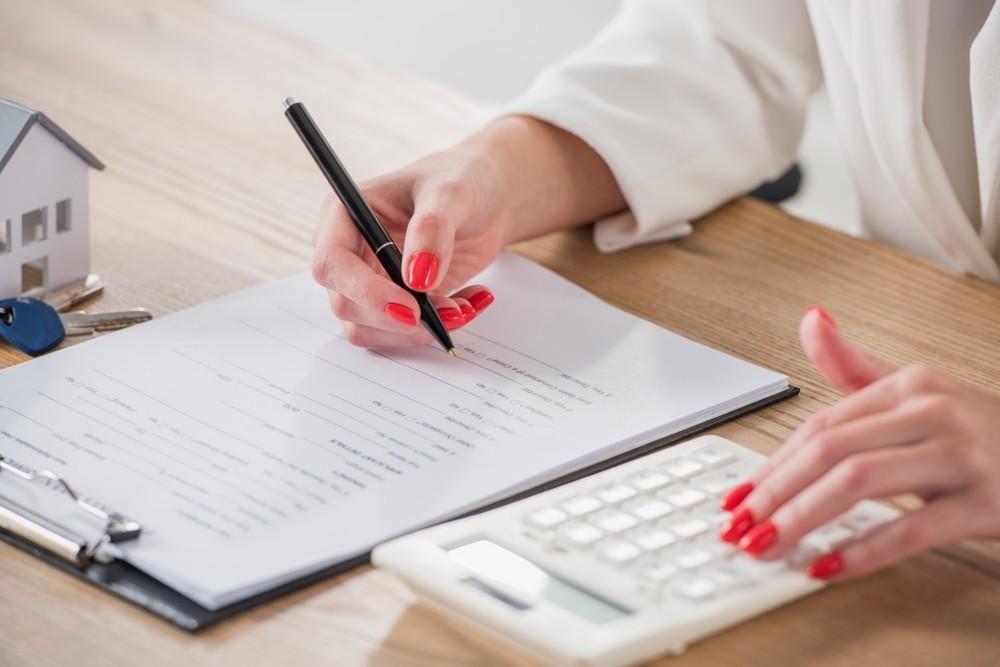mujer haciendo cálculo con papel y calculadora
