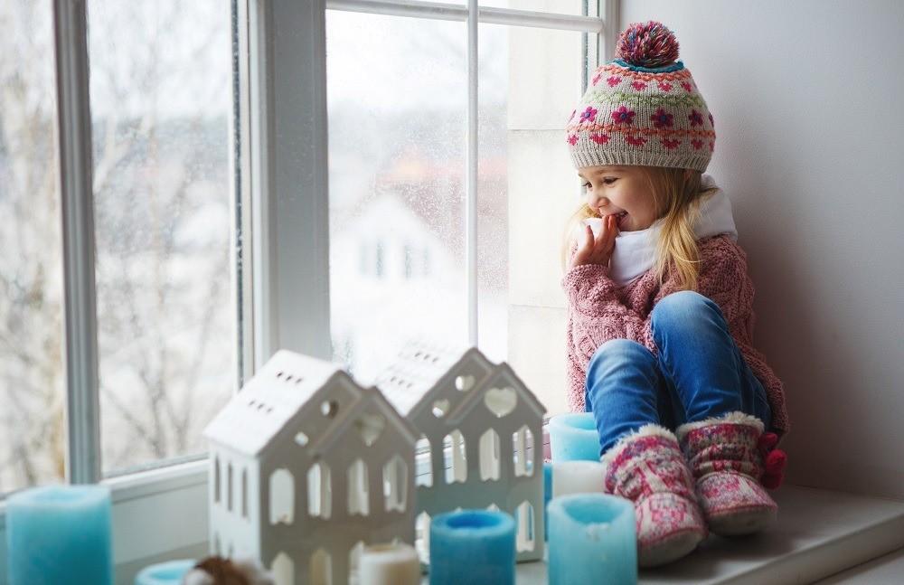 niña junto a ventana
